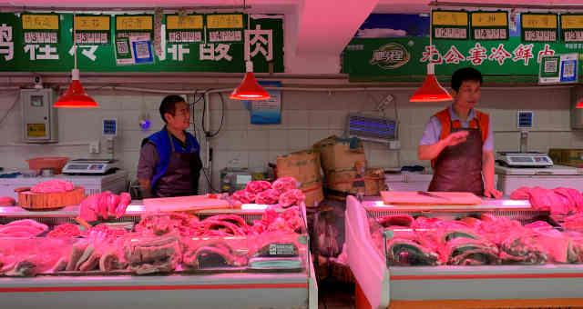 Venda de carne suína em mercado em Pequim, China