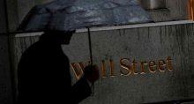 Homem caminha pela chuva em Wall Street do lado de fora da Bolsa de Nova York (NYSE), EUA. 09/10/2019. REUTERS/Brendan McDermid