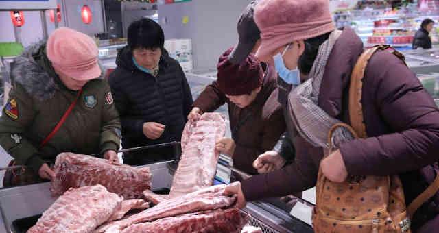 Consumidores selecionam carne de porco congelada em Nantong, China