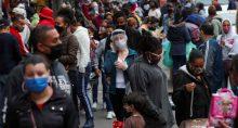 Mulher usando máscara protetora e protetor facial fala ao telefone enquanto pessoas caminham em uma popular rua comercial em meio ao surto de Covid-19 em São Paulo, Brasil, 15 de julho de 2020. REUTERS/Amanda Perobelli