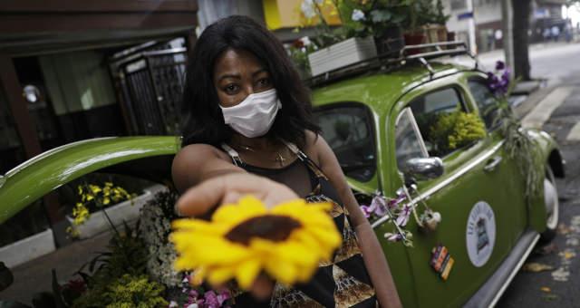 Valcineia Machado ao lado do fusca que transformou em floricultura no Rio de Janeiro