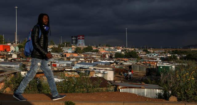 Homem passa por um assentamento informal