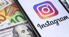 Um celular com o ícone do Instagram ao lado de cédulas de dinheiro, incluindo dólar