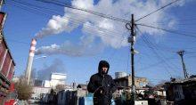 Homem caminha ao lado de usina de energia movida a carvão em Harbin, na China