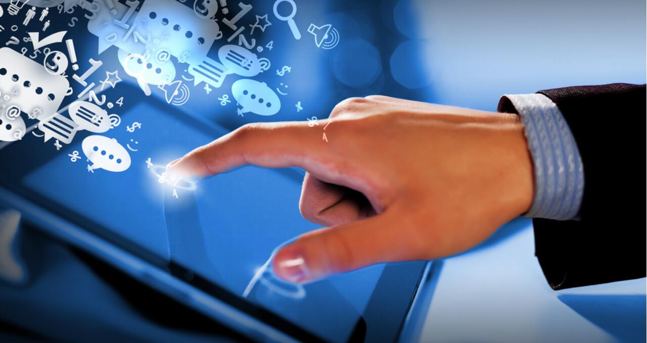 Mão tocando num tablet com ícones relacionados ao marketing digital saindo da tela