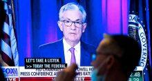 Operador trabalha diante de tela com trasmissão de fala do chair do Fed, Jerome Powell