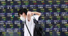 Homem passa por painel eletrônico com informações acionárias em uma corretora em Tóquio