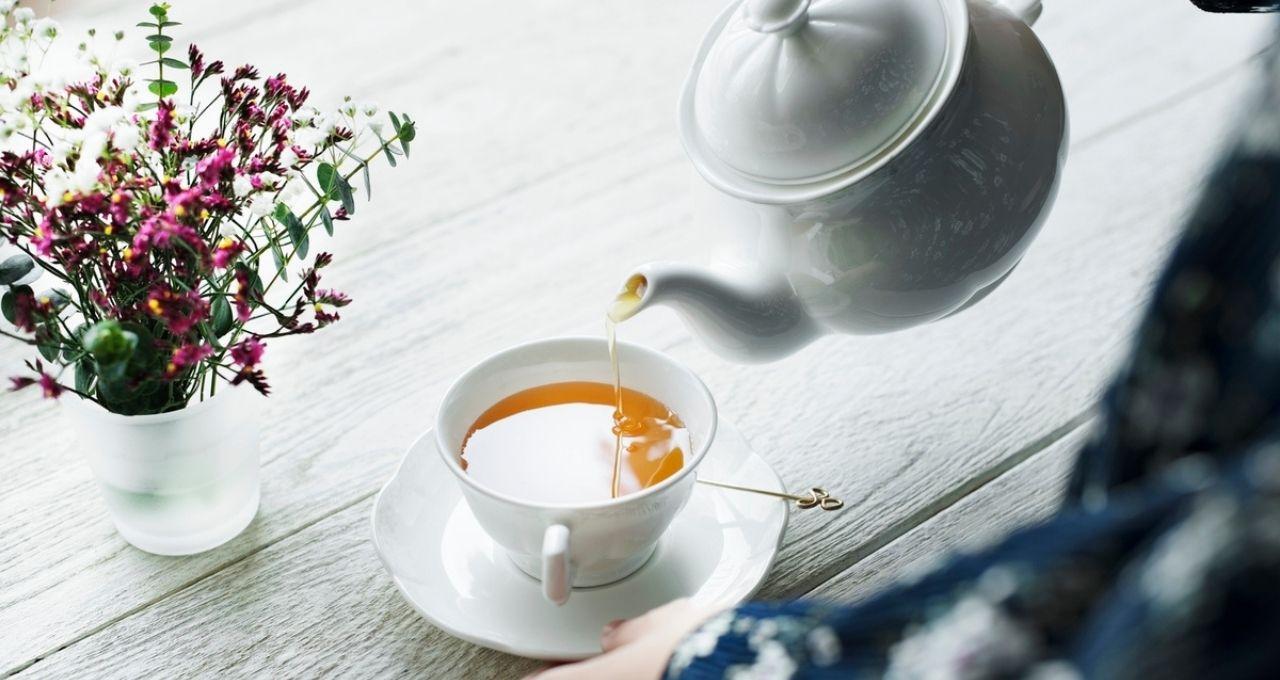 Um bule branco está servindo chá em uma xícara branca